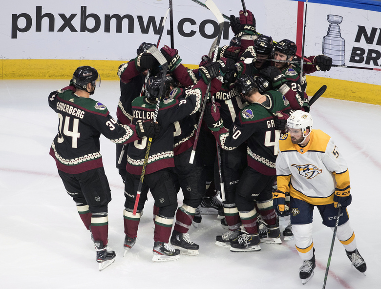 Nashville Predators ' Dante Fabbro (57) skates past as the Arizona Coyotes celebrate their win following overtime in an NHL hockey playoff game Friday, Aug. 7, 2020, in Edmonton, Alberta. (Jason Franson/Canadian Press via AP)