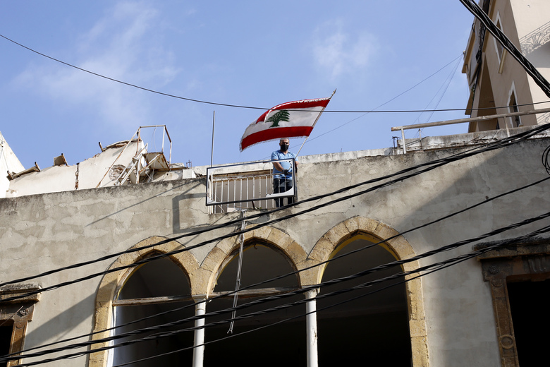 A man puts a Lebanese flag on a roof of a damaged building at a neighborhood near the scene of Tuesday's explosion that hit the seaport of Beirut, Lebanon, Friday, Aug. 7, 2020. Rescue teams were still searching the rubble of Beirut's port for bodies on Friday, nearly three days after a massive explosion sent a wave of destruction through Lebanon's capital. (AP Photo/Thibault Camus)
