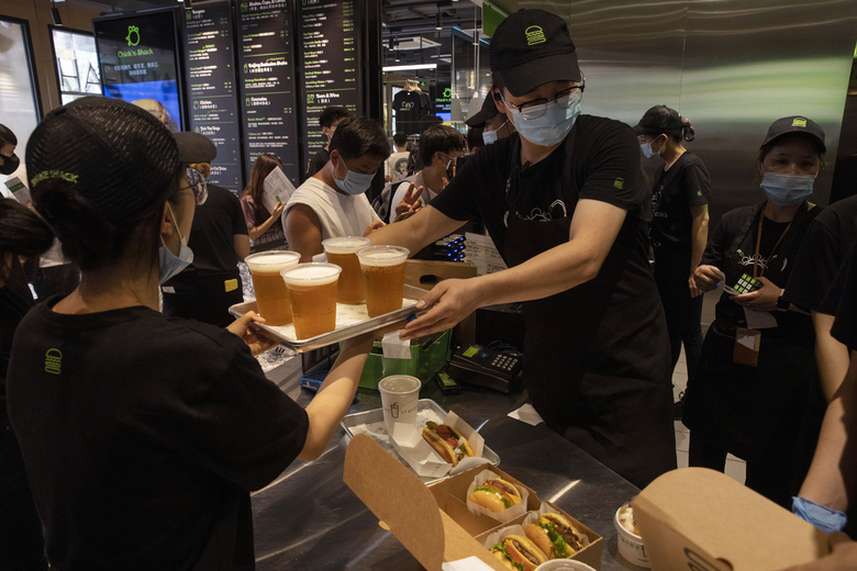 Workers serve beer at the opening of the first Beijing outlet for Shake Shack in Beijing on Wednesday, Aug. 12, 2020. The U.S. headquartered burger chain is opening its first Beijing restaurant at a time when China and the U.S. are at loggerheads over a long list of issues. (AP Photo/Ng Han Guan)