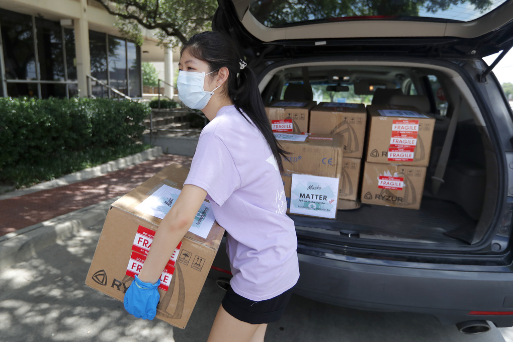 Valerie Xu, 15, delivers donated boxes of masks to a medical center in Dallas in June. (AP Photo/Tony Gutierrez)