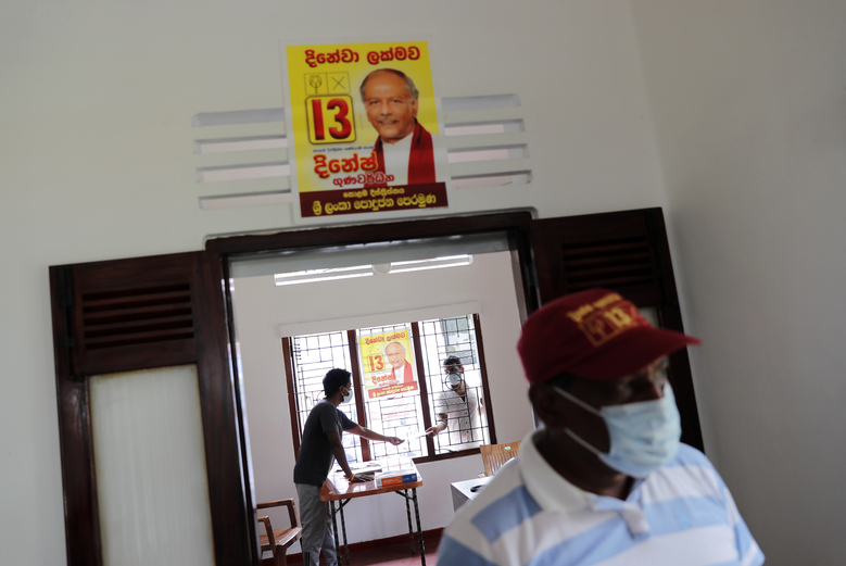 Election propaganda of Sri Lanka's Foreign Minister Dinesh Gunawardena is seen pasted on a wall at a party office in Colombo, Sri Lanka, Monday, July 27, 2020. Sri Lankans are voting in parliamentary elections Wednesday that are expected to strengthen President Gotabaya Rajapaksa's grip on power. Parts of the party are also calling for a two-thirds majority in Parliament so it can amend the constitution to restore presidential powers curbed by a 2015 constitutional change. (AP Photo/Eranga Jayawardena)