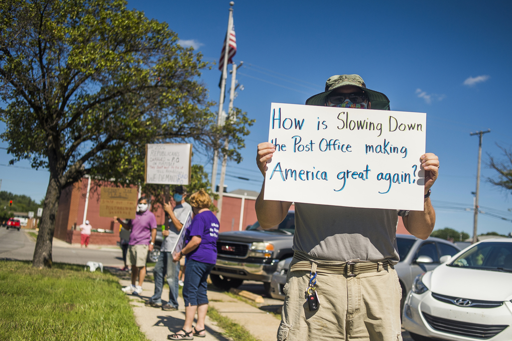 Eric Severson holds a sign as a few dozen people gather Aug. 11 in front of a United States Post Office in Midland, Mich., to protest recent changes to the U.S. Postal Service under new Postmaster General Louis DeJoy. (Katy Kildee / Midland Daily News via AP)