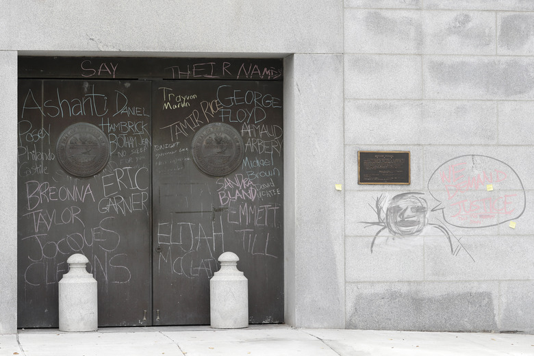 "Graffiti from demonstrators protesting social injustice is left on doors and a wall at the state capitol Wednesday, July 1, 2020, in Nashville, Tenn. Tennessee's newest law, a wide range of crimes commonly associated with protests will see a big bump in penalties and fines, but the most contentious element focuses on escalated penalties for ""illegal camping"" on state property from a misdemeanor to a felony, punishable by up to six years in prison.  (AP Photo/Mark Humphrey)"