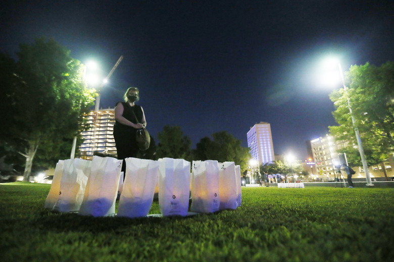In this Thursday, July 30, 2020 photo, Mary Stockwell-White pauses at the 23 luminarias lit at Cleveland Square Park honoring the victims of the Aug. 3, 2019 El Paso shooting, in downtown El Paso. Stockwell-White is a registered nurse from Bellingham, Wash., who is passing through and wanted to pay her respects to the community for the anniversary. (Briana Sanchez/The El Paso Times via AP)