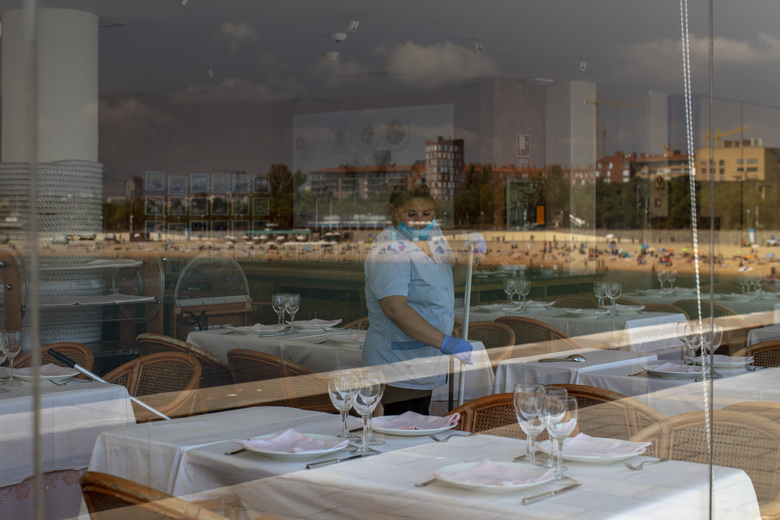 FILE – In this June 29, 2020, file photo, a woman cleans a restaurant prior to the opening, near the beach which is reflected in the glass, in Barcelona, Spain. America's failure so far to contain the spread of the coronavirus as it moves across the country has been met with astonishment and alarm on both sides of the Atlantic. (AP Photo/Emilio Morenatti, File)