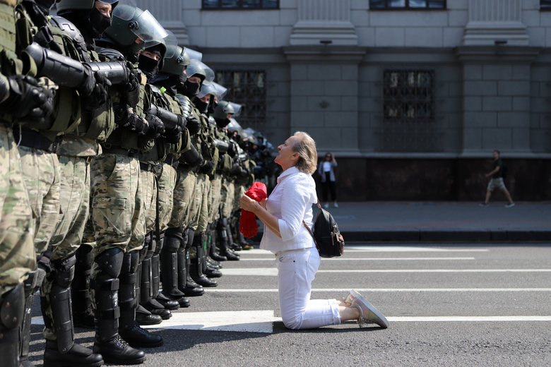 A woman kneels in front of a riot police line as they block Belarusian opposition supporters rally in the center of Minsk, Belarus, Sunday, Aug. 30, 2020. Opposition supporters whose protests have convulsed the country for two weeks aim to hold a march in the capital of Belarus. (AP Photo)