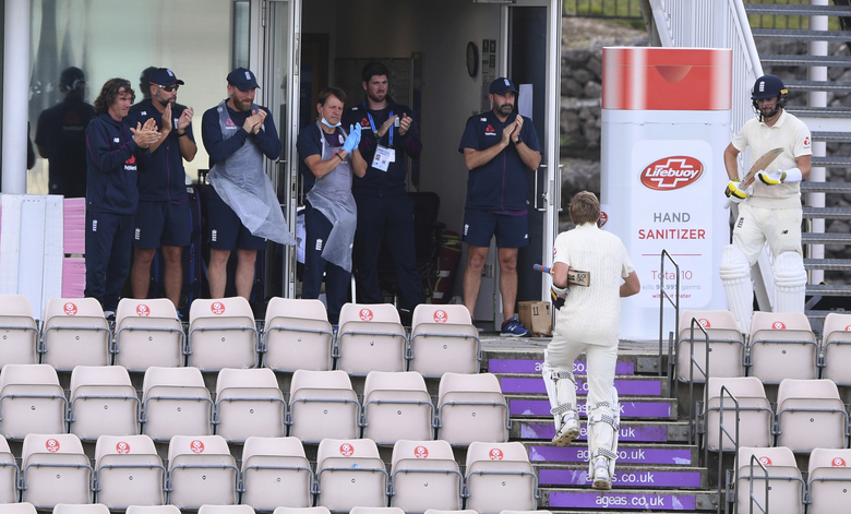 Members of team support staff applaud as England's Zak Crawley, second right, walks back to the dressing room after losing his wicket during the second day of the third cricket Test match between England and Pakistan, at the Ageas Bowl in Southampton, England, Saturday, Aug. 22, 2020. (Mike Hewitt/Pool via AP)