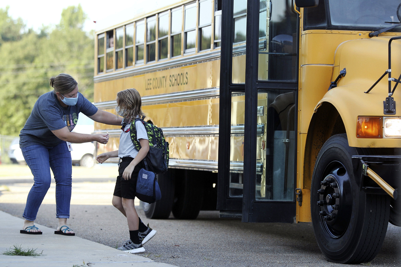 FILE – In this Aug. 6, 2020, file photo, Audrey Wylie, a speech pathologist, at Saltillo Primary School, puts a bus number sticker on Cruz Antle, a first grader, as he gets off the bus for his first day back to school in Saltillo, Miss. As schools reopen around the country, their ability to quickly identify and contain coronavirus outbreaks before they get out of hand is about to be put to the test. (Adam Robison/The Northeast Mississippi Daily Journal via AP, File)