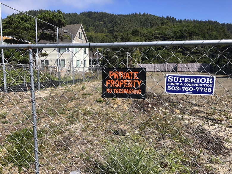 Facebook's cable landing site is seen on a residential lot located within the high fence at the tiny village of Tierra del Mar, Ore., Monday, Aug. 17, 2020. Facebook's effort to build a landing site in a village on the Oregon coast for a fiber optic cable linking Asia and North America has run into serious trouble. First, a drill pipe snapped under the seabed. Workers left 1,100 feet of pipe, 6,500 gallons of drilling fluid, a drill tip and other materials under the seabed as they closed down the site, aiming to try again next year. (AP Photo/Andrew Selsky)