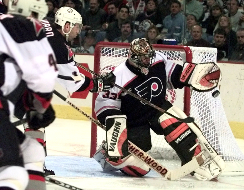 FILE – In this April 16, 2000, file photo, Philadelphia Flyers goalie Brian Boucher makes a save on a shot by Buffalo Sabres left wing Dixon Ward during the second period of an NHL hockey playoff game in Buffalo, N.Y. Boucher had a front-row seat to the five-overtime game between the Tampa Bay Lightning and Columbus Blue Jackets on Tuesday, Aug. 11, 2020. Boucher was working it as the between-the-benches analyst for NBC Sports, 20 years after he played goal in a five-overtime game himself, in May 2000 against the Pittsburgh Penguins. (AP Photo/Don Heupel, File)