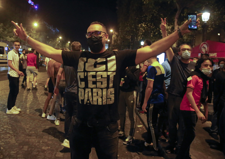 A supporter of the Paris Saint Germain soccer team celebrates on the Champs Elysee in Paris, Tuesday, Aug. 18, 2020 after his team won 3-0 against RB Leipzig. Shirt reads, here is Paris. (AP Photo/Michel Euler)