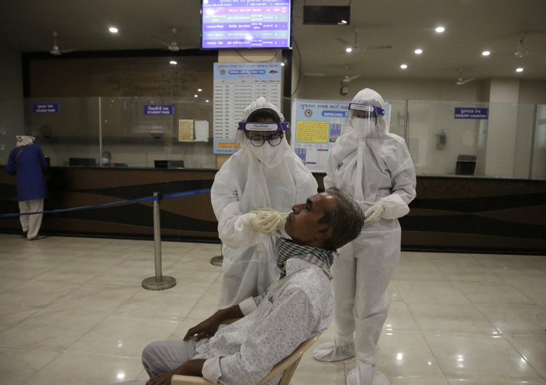 A health worker takes a nasal swab sample to test for COVID-19 at a state bus station in Ahmedabad, India, Saturday, Aug. 29, 2020. India has the third-highest coronavirus caseload after the United States and Brazil, and the fourth-highest death toll in the world. (AP Photo/Ajit Solanki)