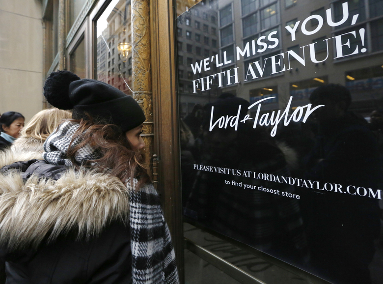 FILE – In this Jan. 2, 2019 file photo, women peer in the front door of Lord & Taylor's flagship Fifth Avenue store which closed for good,  in New York. A slew of once-beloved brands from Lord & Taylor to Ann Taylor have filed for Chapter 11 since the pandemic. Many shoppers will see these iconic labels vanish or become mere shadows of themselves as they drastically shrink their businesses or get acquired. But while loyal customers bemoan their loss, the brands themselves have been clearly losing favor for year.  (AP Photo/Kathy Willens, File)