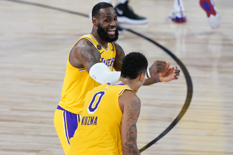 Los Angeles Lakers' Kyle Kuzma (0) is congratulated by LeBron James after hitting a game-winning 3-pointer against the Denver Nuggets during the second half of an NBA basketball game Monday, Aug. 10, 2020, in Lake Buena Vista, Fla. The Lakers won 124-121. (AP Photo/Ashley Landis, Pool)