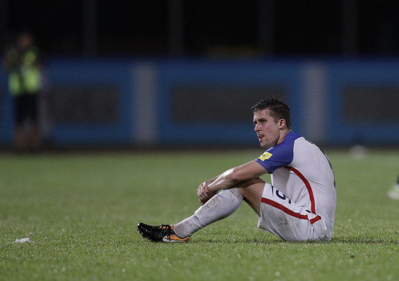 File-United States' Matt Besler, squats on the pitch after losing 2-1 against Trinidad and Tobago during a 2018 World Cup qualifying soccer match in Couva, Trinidad, Tuesday, Oct. 10, 2017.  The United States could start qualifying for the 2022 World Cup in Trinidad, where the Americans flopped on the final night three years ago and failed to reach the 2018 tournament. (AP Photo/Rebecca Blackwell, File)