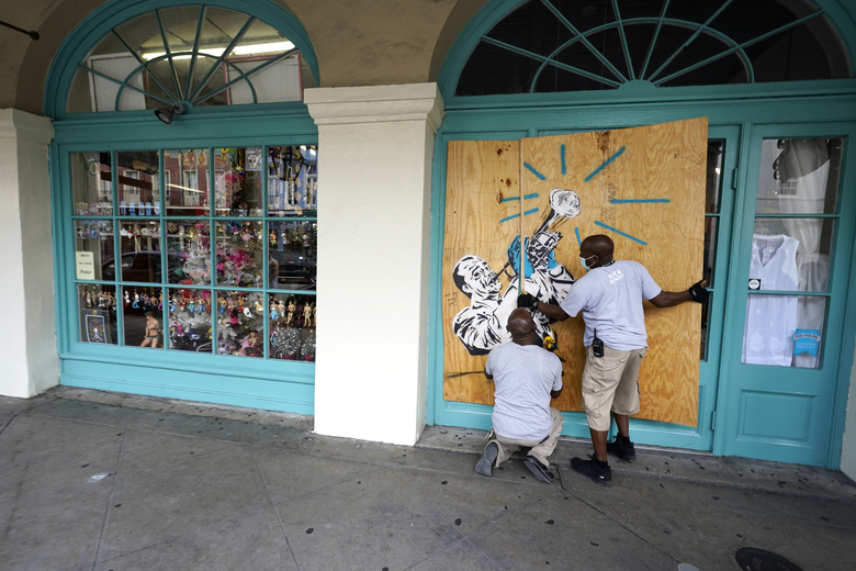 Workers board up shops in the French Quarter of New Orleans, Sunday, Aug. 23, 2020, in advance of Hurricane Marco, expected to make landfall on the Southern Louisiana coast. (AP Photo/Gerald Herbert)