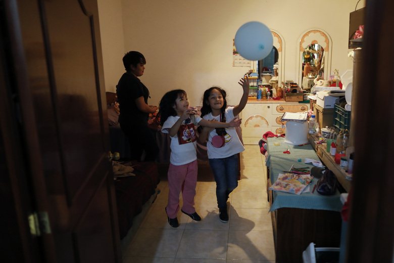 Jose Juan Serralde's daughters play in the room where his parents lived until their deaths in May from COVID-19, in San Gregorio Atlapulco, Xochimilco, Mexico City, Wednesday, July 29, 2020.  Mexico recommended people self-quarantine starting in mid-March, but the elderly couple continued visiting markets to sell the plants they grew in a greenhouse, and they did not wear masks, while the family continued to live in tight quarters where most of the family got COVID-19, but recovered. (AP Photo/Rebecca Blackwell)