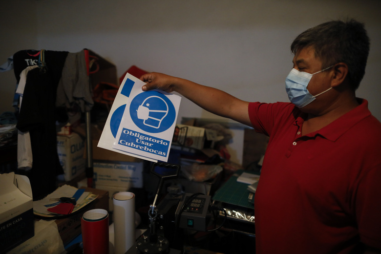 "Jose Juan Serralde holds up decals his family prints and sells to neighboring businesses, showing a figure with a face mask with the Spanish slogan ""Using a face mask is obligatory,"" at his home where his parents fell ill of COVID-19 and died two months prior, in San Gregorio Atlapulco, Xochimilco, Mexico City, Wednesday, July 29, 2020. Serralde said he wishes authorities would enforce the virus-control measures that businesses are supposed to implement and make face masks mandatory. ""I feel like this is slipping out of the hands of the government, the mayor, the president, everyone,"" he said. (AP Photo/Rebecca Blackwell)"