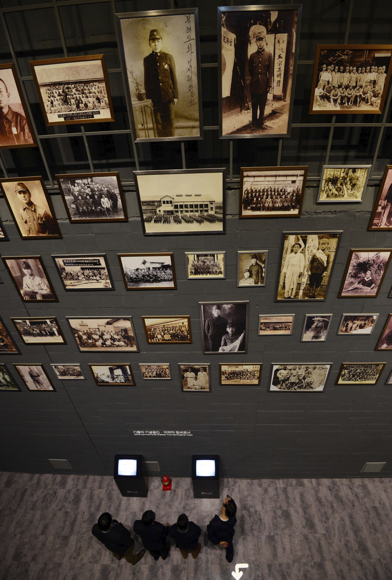 In this Dec. 10, 2015, photo, photos of victims of forced labor during Japan's colonial rule of the Korean Peninsula are displayed at National Memorial Museum of Forced Mobilization under Japanese Occupation in Busan, South Korea. Many Koreans today think Japan still hasn't fully acknowledged responsibility for its atrocities, and survivors of its forced labor and prostitution are still seeking Japan's atonement. (Ha Kyung-min/Newsis via AP)