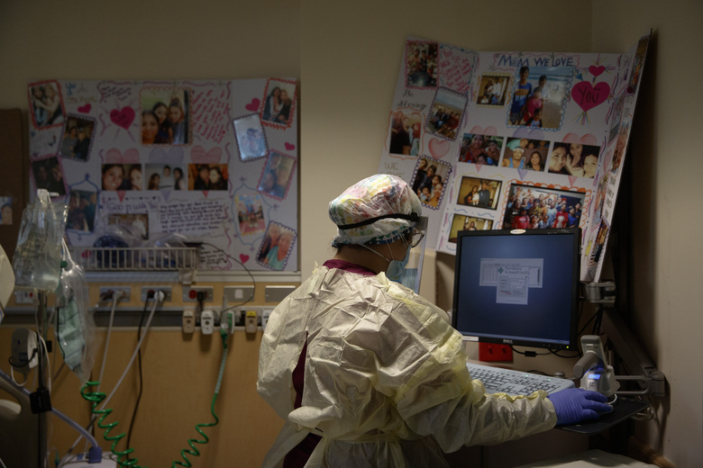 """Nurse Sarvnaz Michel, 28, works on a computer while assisting a COVID-19 patient in a room with poster boards filled with family photos and get-well messages at St. Jude Medical Center in Fullerton, Calif., Friday, July 10, 2020. The 28-year-old's career has forced her to blur and blend her two lives. She agonizes over her every move in the hospital — """"Did I put my gear on the right way, did I take it off the right way, did I touch something wrong accidentally?"""" — and locks her shoes in the car after her shifts. (AP Photo/Jae C. Hong)"""