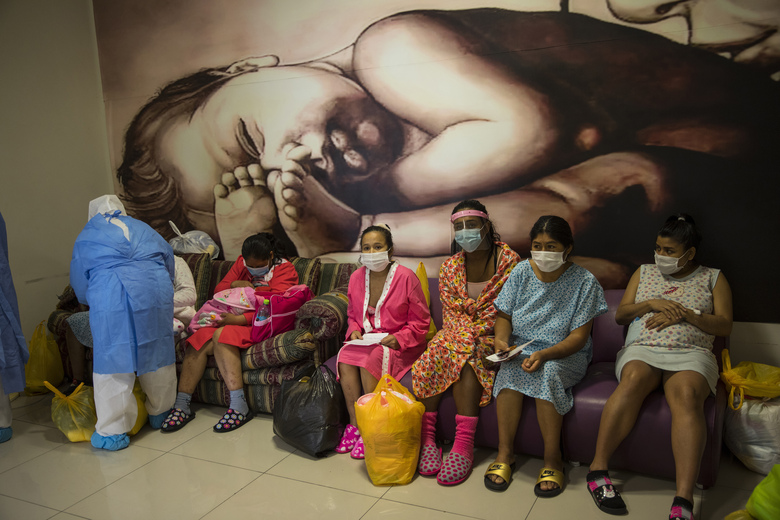 Maria Alvarez, 24, center, sits with other mothers who are infected with the new coronavirus, as they wait to be handed their babies before being discharged at the National Perinatal and Maternal Institute in Lima, Peru, Thursday, July 30, 2020. Between April and the start of August, more than 2,000 infected patients gave birth here, with more than 100 newborns testing positive. (AP Photo/Rodrigo Abd)