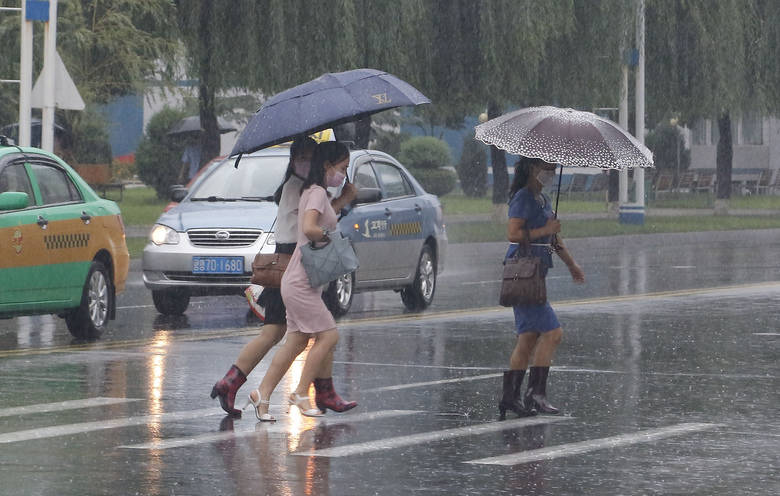 Women walk with umbrellas during torrential rains, Wednesday, August 5, 2020, in Pyongyang. North Korea says torrential rains have lashed the country, prompting outside worries about possible big damages in the impoverished country. (AP Photo/Cha Song Ho)