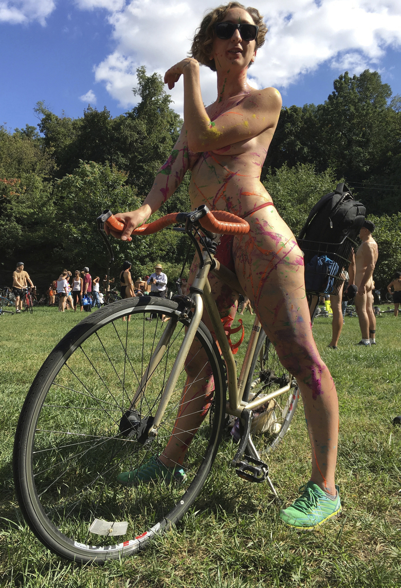 FILE—In this file photo from Sept. 9, 2017, Olivia Neely, a topless cyclist wearing body paint, motions before the start of that year's annual Philly Naked Bike Ride in Philadelphia. Organizers who'd been gearing up for this year's event that usually draws thousands of nude cyclists for a trip around Philadelphia and its tourist sites said Friday, Aug. 14, 2020 that the city's COVID-19 cases made them halt their planning and slam the brakes on the scheduled Aug. 29 date. (AP Photo/Dino Hazell, File)