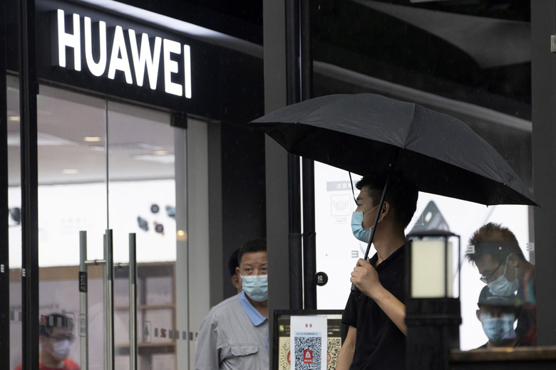 A man wearing a mask to protect from the coronavirus walks with an umbrella as it rains outside a Huawei store in Beijing on Wednesday, Aug. 5, 2020. For nearly a decade, Huawei kept worldwide sales growing as Washington told U.S. phone companies not to buy its network equipment and lobbied allies to reject China's first global tech brand as a security threat. (AP Photo/Ng Han Guan)