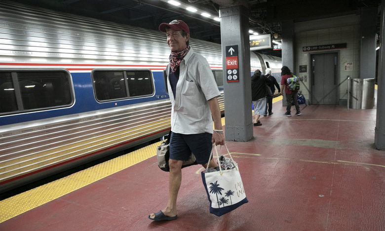 """Timothy Mahyna arrives on a train from Georgia at Amtrak's Penn Station, Thursday, Aug. 6, 2020, in New York. Mayor de Blasio is asking travelers from 34 states, including Georgia where COVID-19 infection rates are high, to quarantine for 14 days after arriving in the city. Mahyna, from Syracuse, N.Y., said, """"I will probably quarantine for a week when I get home."""" (AP Photo/Mark Lennihan)"""