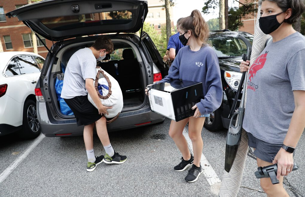 Miranda Darwin, from Raleigh and a freshman at UNC-Chapel Hill, center, gets help from her brother, Sam, and her mother, Stacy, while moving out of her room Aug. 18, 2020, at Hinton James residence hall in Chapel Hill, N.C. As more and more schools and businesses around the country get the OK to reopen, some college towns are moving in the opposite direction because of too much partying and too many COVID-19 infections among students. (Ethan Hyman/The News & Observer via AP)