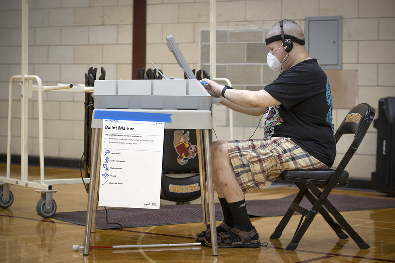 Jason White, who is visually impaired, uses the AutoMARK voting machine to cast his vote at the Roosevelt High School polling location, Tuesday, August 11, 2020 in Minneapolis, Minn. (Elizabeth Flores/Star Tribune via AP)