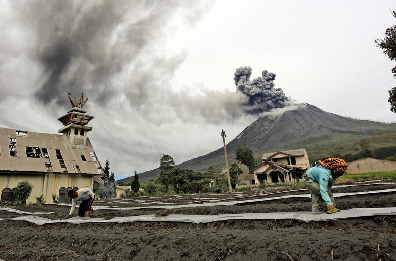 """Villagers work at their farm as Mount Sinabung spews volcanic materials during an eruption, in Karo, North Sumatra, Indonesia Friday, Aug. 14, 2020. Sinabung is among more than 120 active volcanoes in Indonesia, which is prone to seismic upheaval due to its location on the Pacific """"Ring of Fire,"""" an arc of volcanoes and fault lines encircling the Pacific Basin. (AP Photo)"""