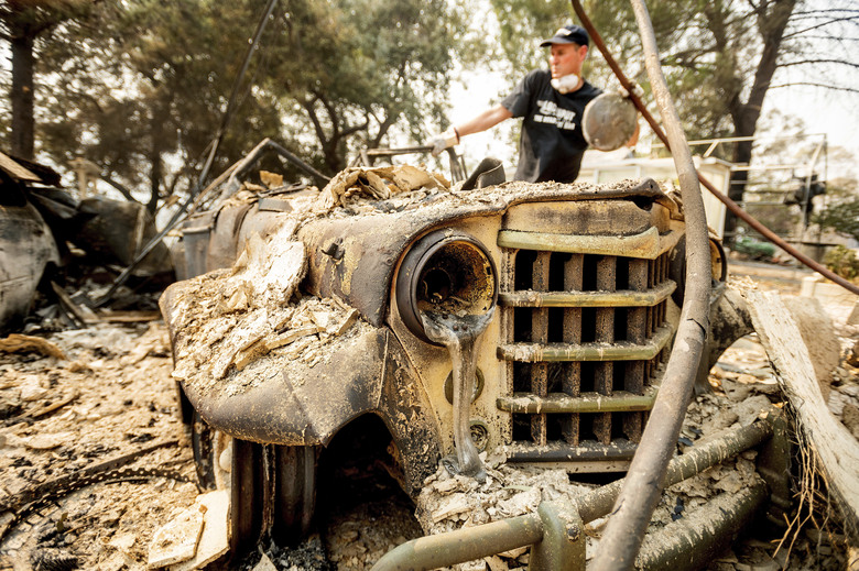 Mark Hanson goes through the remains of a 1951 Willys-Overland Jeepster following the LNU Lightning Complex fires in Vacaville, Calif., on Friday, Aug. 21, 2020. The blaze destroyed his family home as well as the Jeepster which his father purchased new and Mark rebuilt while in high school. (AP Photo/Noah Berger)