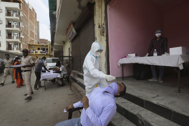 FILE – In this Aug. 7, 2020, file photo, a health worker takes a nasal swab sample for a COVID- 19 antigen test, in New Delhi, India. In June, India began using the cheaper, faster but less accurate tests to scale up testing for the coronavirus — a strategy that the U.S. is now considering. (AP Photo/Manish Swarup, File)