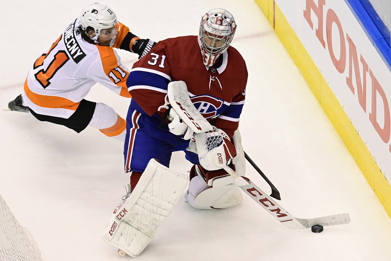 Philadelphia Flyers right wing Travis Konecny (11) looks for an opportunity as Montreal Canadiens goaltender Carey Price (31) clears the puck from behind the net during the second period of Game 3 of an NHL hockey playoff first-round series Sunday, Aug. 16, 2020, in Toronto. (Frank Gunn/The Canadian Press via AP)