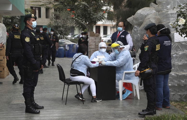 Police officers test a woman who was detained at a disco where thirteen people died during a stampede, for COVID-19 in Lima, Peru, Sunday, Aug. 23, 2020. Officials said the stampede happened at a disco after a police raid to enforce the country's lockdown during the coronavirus pandemic. (AP Photo/Martin Mejia)