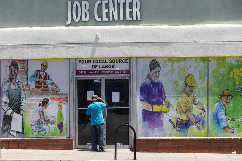 FILE – In this May 7, 2020, file photo, a person looks inside the closed doors of the Pasadena Community Job Center in Pasadena, Calif., during the coronavirus outbreak. On Thursday, Aug. 20, the government reported that the number of workers applying for unemployment climbed back over 1 million last week after two weeks of declines. (AP Photo/Damian Dovarganes, File)