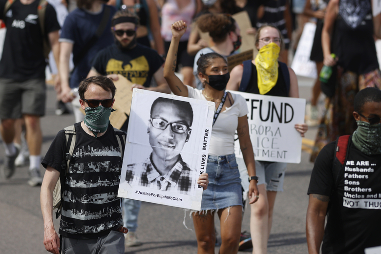 FILE – In this June 27, 2020 file photo, demonstrators carry placards as they walk down Sable Boulevard during a rally and march over the death of Elijah McClain in Aurora, Colo.  Interim chief Vanessa Wilson was chosen Monday, Aug. 3 as the new chief of the Aurora Police Department, looking to regain public trust following a tumultuous year filled with scrutiny after the death of McClain, a Black man officers stopped on the street and put into a chokehold. (AP Photo/David Zalubowski, File)