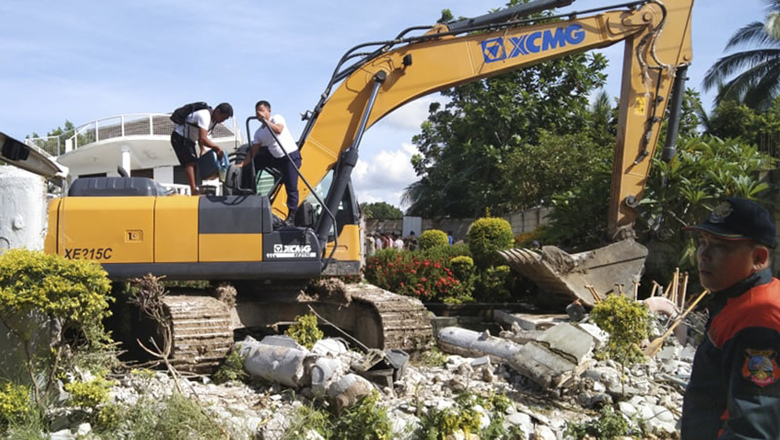 Men refuel a backhoe being used to sift through the rubble after a strong earthquake struck Cataingan, Masbate province, central Philippines, Tuesday Aug. 18, 2020. A powerful and shallow earthquake struck a central Philippine region Tuesday, prompting people to dash out of homes and offices but there were no immediate reports of injuries or major damage. (AP Photo/Christopher Decamon)