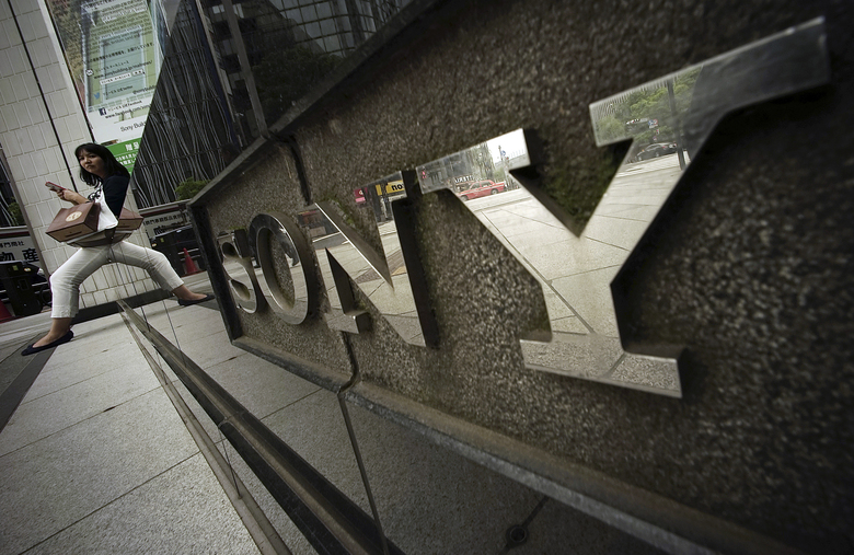 FILE – In this April 30, 2015, file photo, a woman sits near the logo of Sony Corp. in Tokyo. Japanese electronics and entertainment company Sony Corp. said Tuesday that its April-June profit jumped 53% as its video-game and other online businesses thrived with people staying home due to the coronavirus pandemic. (AP Photo/Eugene Hoshiko, File)