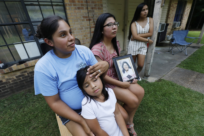 Sisters Kristi Wishork, left, consoles her daughter Renaya Farmer, 5, as she and her sisters Kristina Taylor, center and Kaydee Taylor, right recall the family pride and love their late mother, Sharon Taylor, had for their family, Tuesday, July 21, 2020 outside the family home in Tucker, Miss. Sharon Taylor, 53, died of coronavirus at the University of Mississippi Medical Center in Jackson on June 26 after two weeks in the hospital and never saw her daughter Kristina, the class valedictorian at Choctaw Central High School, graduate. (AP Photo/Rogelio V. Solis)