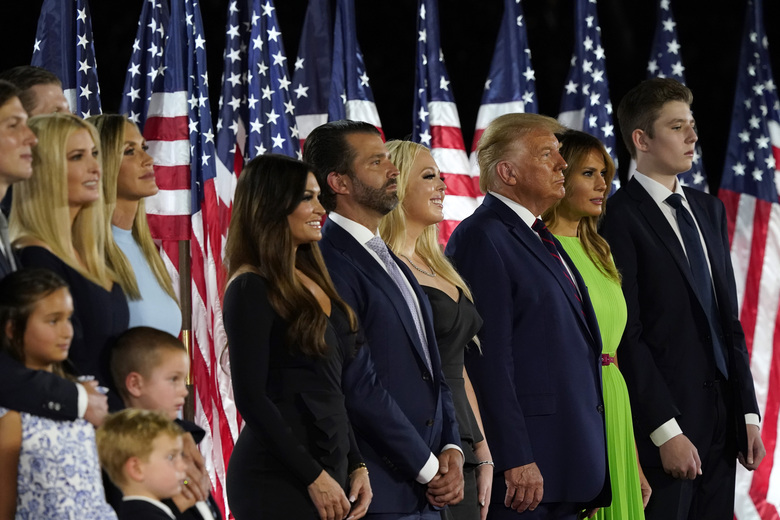 From left, Jared Kushner and his wife Ivanka Trump, Eric and Lara Trump, Kimberly Guilfoyle and Donald Trump Jr., Tiffany Trump, President Donald Trump and first lady Melania Trump and Barron Trump stand on stage on the South Lawn of the White House on the fourth day of the Republican National Convention, Thursday, Aug. 27, 2020, in Washington. (AP Photo/Alex Brandon)