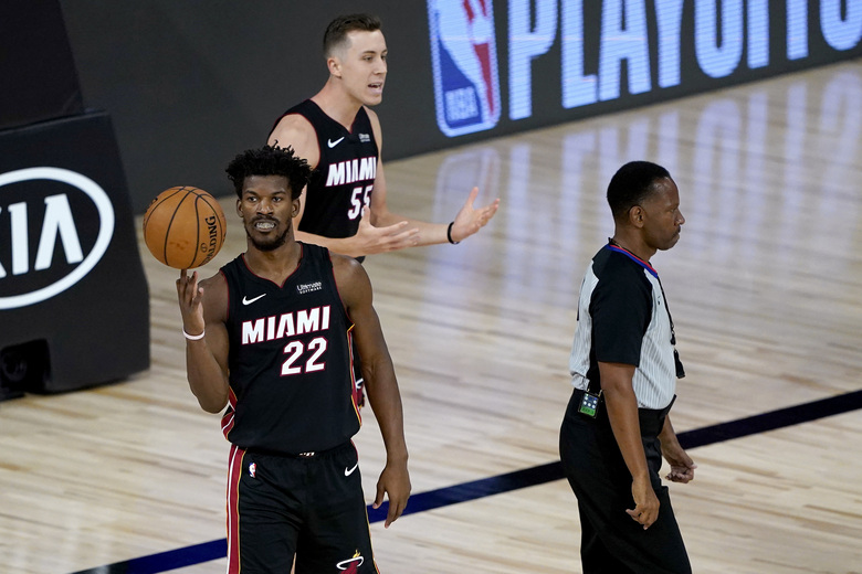 Miami Heat's Jimmy Butler (22) spins the ball as teammate Duncan Robinson (55) argues a call with the referee during the first half of an NBA basketball first round playoff game against the Indiana Pacers, Thursday, Aug. 20, 2020, in Lake Buena Vista, Fla. (AP Photo/Ashley Landis, Pool)
