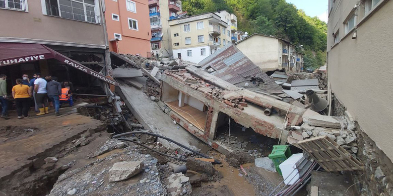 People inspect the destruction after floods caused by heavy rain in the mountain town of Dereli in Giresun province, along Turkey's Black Sea coastline, Sunday, Aug. 23, 2020.  Interior Minister Suleyman Soylu said four people have died and 11 people are still missing after flooding around Dereli.(AP Photo)