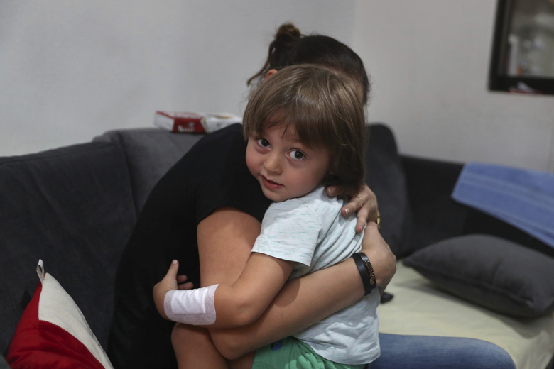 CORRECTS THE FAMILY NAME OF THE BOY – Hiba Achi hugs her son, three-year-old Abed Itani, at her house in Beirut, Lebanon, Tuesday, Aug. 11, 2020. Abed was playing with his Lego blocks when the huge blast ripped through Beirut, shattering the nearby glass doors. He had cuts on his tiny arms and feet, a head injury, and was taken to the emergency room, where he sat amid other bleeding people. (AP Photo/Bilal Hussein)