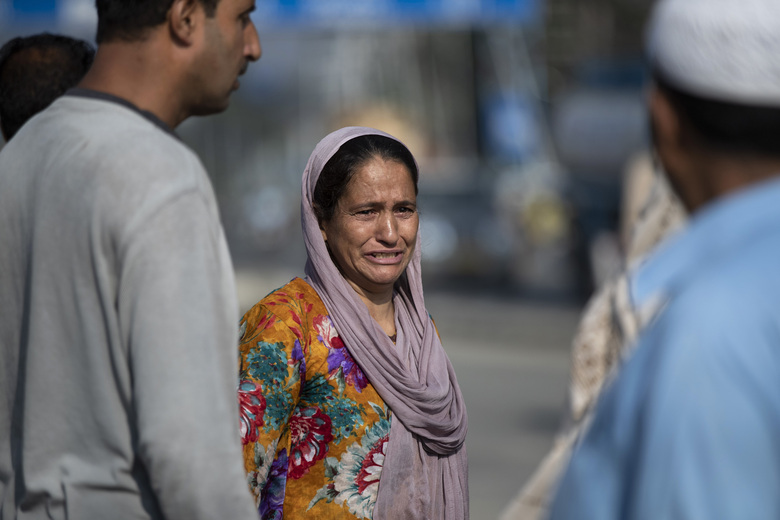 A Kashmiri woman weeps near a gun battle site on the outskirts of Srinagar, Indian controlled Kashmir, Sunday, Aug. 30, 2020. Three suspected rebels and a counterinsurgency police officer were killed in a gun-battle in the outskirts of Indian-controlled Kashmir's main city, police said Sunday. (AP Photo/Mukhtar Khan)