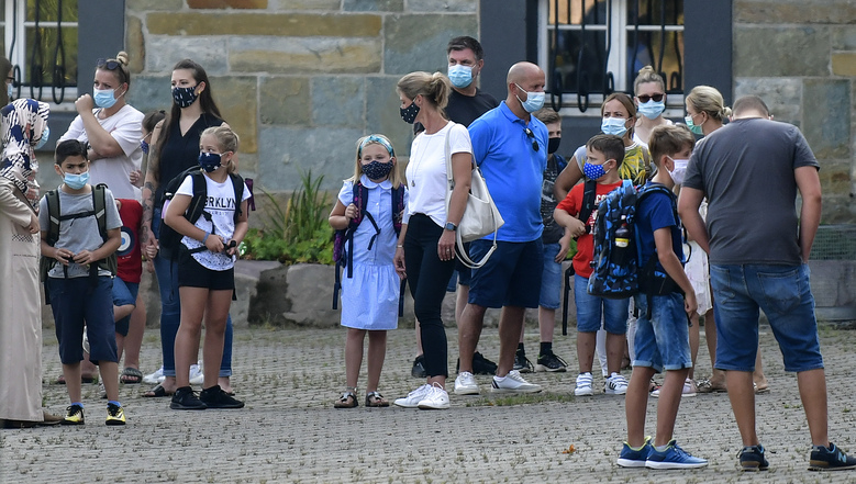 Parents wait with their children for the start of their first day of school in Gelsenkirchen, Germany. Despite a spike in coronavirus infections, authorities in Europe are determined to send children back to school.  (AP Photo/Martin Meissner, file)