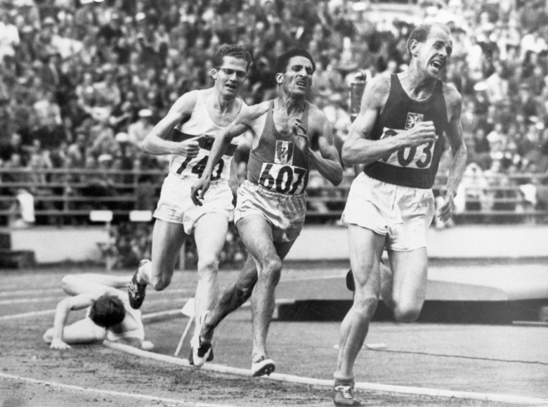"""FILE – In this July 24, 1952, file photo, British athlete Christopher """"Chris"""" Chataway falls as Emil Zatopek of Czechoslovakia, followed by Alain Mimoun of France and German bronze medal winner Herbert Schade, leads near the end of the Men's final 5000 meter race at the Summer Olympic Games on in Helsinki, Finland. (AP Photo/File)"""
