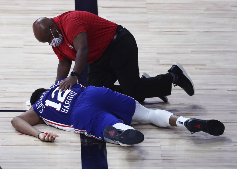 Philadelphia 76ers forward Tobias Harris (12) is attended to after hitting his head against the Boston Celtics during the third quarter of Game 4 of an NBA basketball first-round playoff series, Sunday, Aug. 23, 2020, in Lake Buena Vista, Fla. (Kim Klement/Pool Photo via AP)