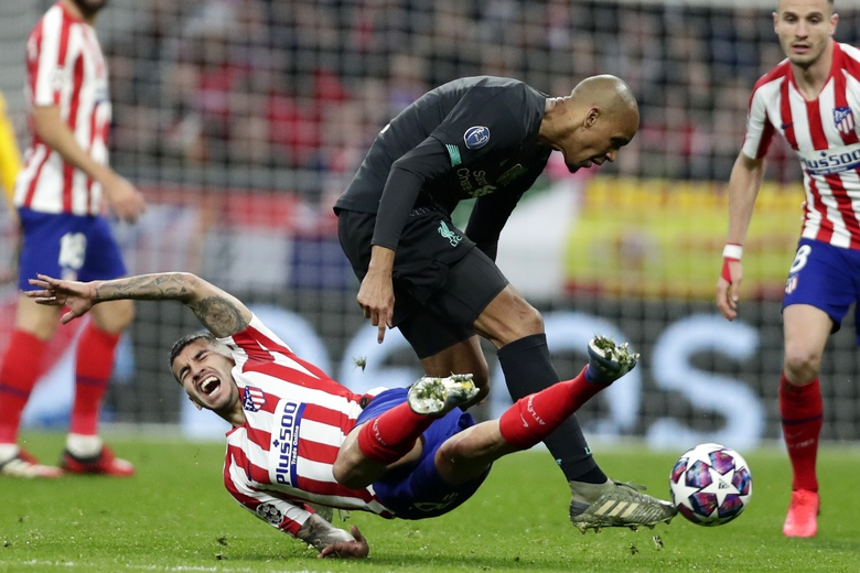 Atletico Madrid's Angel Correa falls as Liverpool's Fabinho goes for the ball during a 1st leg, round of 16, of the Champions League soccer match between Atletico Madrid and Liverpool at the Wanda Metropolitano stadium in Madrid, Tuesday, Feb. 18, 2020. (AP Photo/Manu Fernandez)